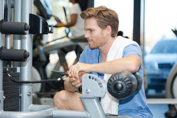 Un jeune sportif règle sa machine de fitness avant de commencer sa séance