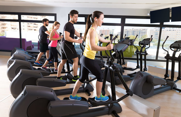 Des sportifs en pleine séance de velo elliptique dans une salle de gym