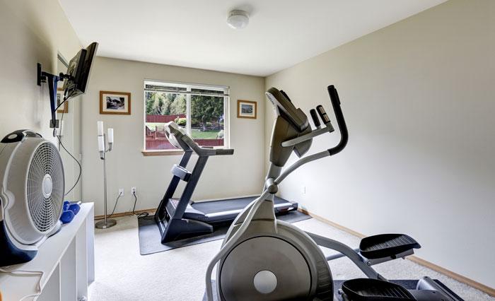 Une salle de sport à la maison avec un tapis de course et un velo elliptique