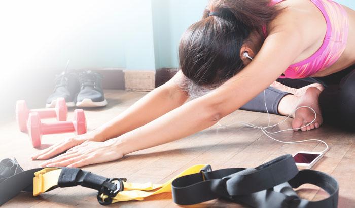 Une sportive s'étire après une séance de sport sur un rameur